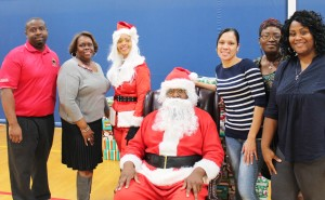 Left, Shadon Wilson, JJK Staff and Marcia Oliver, Center Coordinator for SIUE with Santa and his helper. Three members of Ms. Oliver's staff to the right of Santa, help to make sure that more that 150 Head Start students received a Christmas Gift and additional winter gear like wool caps and gloves.
